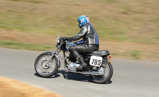 Muž v čiernej koženej bunde a nohaviciach, s modrou prilbou na hlave ide na motorke.jpg