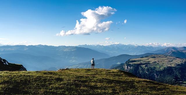 Muž kráča po lúke medzi horami.jpg